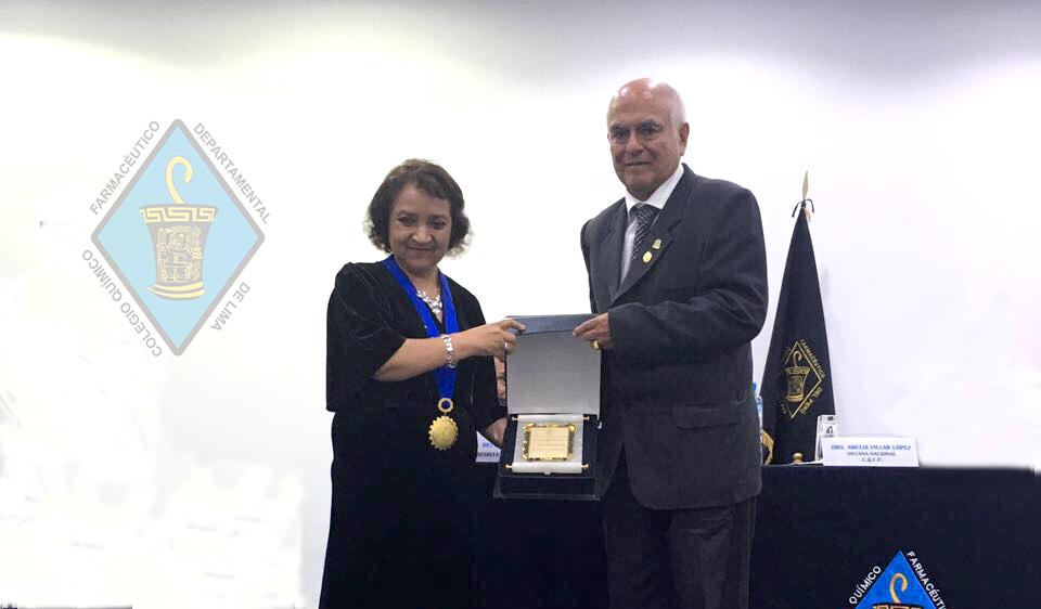 Dra. Rosa Amelia Villar López, Decana del Colegio Químico Farmacéutico del Perú, haciendo la entrega de distinción al Dr. Wilman Ruíz Vigo, Rector de la UPAGU